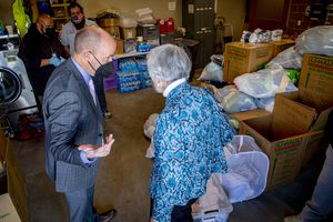 (Isaac Hale | Special to The Tribune) Donated items await to be sorted as Gov. Spencer Cox talks with philanthropist Pamela Atkinson before a press conference held at The Road Home Midvale Family Center on Tuesday, March 2, 2021.