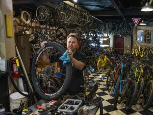(Rick Egan | The Salt Lake Tribune)  Jerks Bike Shop owner Kirk Sherrod works on a bike tire at his store on State Street in Murray on Monday, June 21, 2021.  Bicycles and bike parts have been in short supply due to the increased interest in cycling this past year.