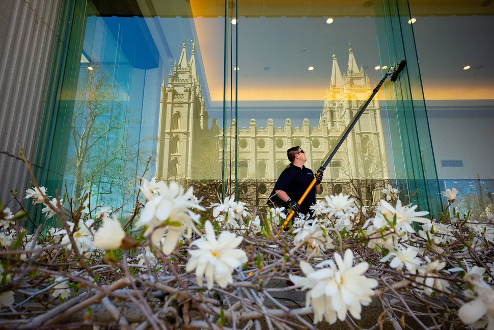 (Trent Nelson | The Salt Lake Tribune) The Salt Lake Temple of The Church of Jesus Christ of Latter-day Saints is reflected in a window of the South Visitors' Center on Temple Square in Salt Lake City on Thursday, April 18, 2019. Washing the window is Christian Dietz.