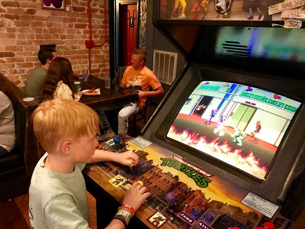(Heather May | Special to The Tribune) Luke, 8, plays at arcade game at Lucky Slice Pizza in Ogden.