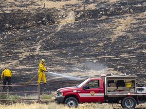 (Rick Egan | The Salt Lake Tribune) Firefighters spray hot spots on a wildfire fire in Herriman on Friday, July 16, 2021. Rep. Blake Moore, R-Utah, is pushing a federal bill to help in the battle against wildfires.
