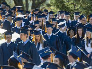 (Rick Egan  |  The Salt Lake Tribune)        Brigham Young University Graduates make their way across the pedestrian bridge to the Marriott Center for the 144th BYU Commencement, Thursday, April 25, 2019.