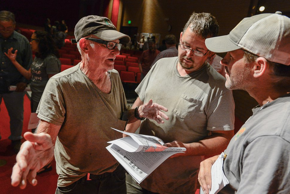 (Francisco Kjolseth | The Salt Lake Tribune) Glen Atwood, left, and his son Treavor speak with Operations Section Chief Dave Vining about the Coal Hollow Fire during a community meeting with the incident management team at Sanpete High School in Mt Pleasant on Thursday, Aug. 9, 2018. The Atwood's have property east of the fire line and had to evacuate.