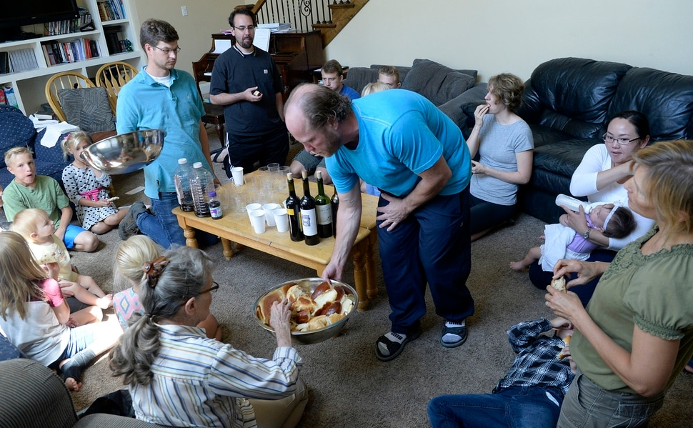 (Al Hartmann | The Salt Lake Tribune) Believers in Denver Snuffer's Remnant movement meet in a Sandy home Sunday, Aug. 13, to sing songs and take the sacrament. Ken Jensen, who is hosting the group, passes the sacrament bread to the group.