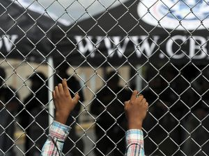 (Fernando Llano   The Associated Press) A migrant leans on a fence of the Gateway International Bridge that connects downtown Matamoros, Mexico, with Brownsville, Thursday, Oct. 10, 2019. Migrants, including a Latter-day Saint couple, seeking asylum in the U.S. wait in Matamoros just across the Rio Grande from Texas.
