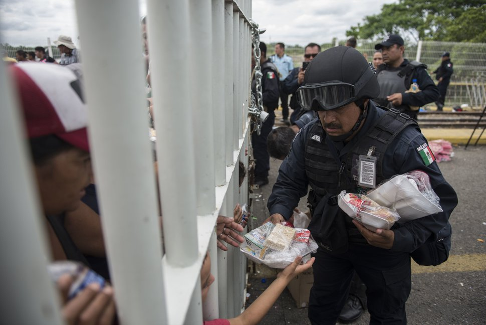 A Mexican Federal Police officer hands out food to Honduran migrants stuck in no man's land on the bridge over the Suchiate River that is the border between Guatemala and Mexico, near Ciudad Hidalgo, Mexico, Saturday, Oct. 20, 2018. The entry into Mexico via the bridge has been closed. The migrants have moved about 30 feet back from the gate that separates them from Mexican police to establish a buffer zone. About 1,000 migrants now remain on the bridge between Guatemala and Mexico. (AP Photo/Oliver de Ros)