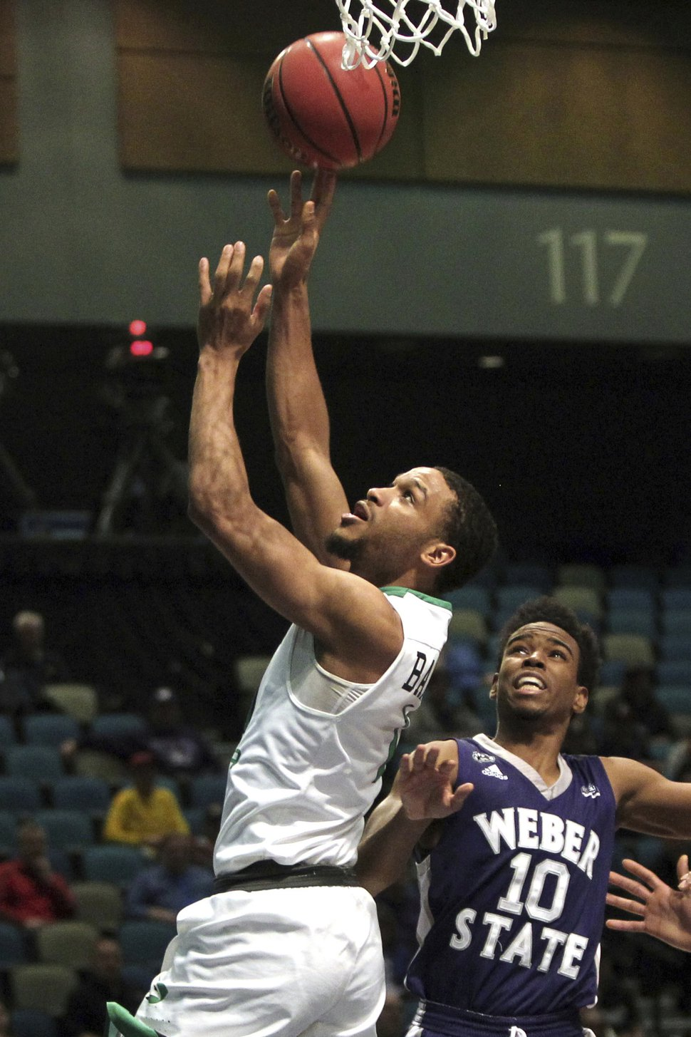 North Dakota guard Corey Baldwinl (1) scores in front of Weber State guard Jerrick Harding (10) during the first half an NCAA college basketball game in the finals of the Big Sky tournament in Reno, Nev., Saturday, March 11, 2017. (AP Photo/Lance Iversen)