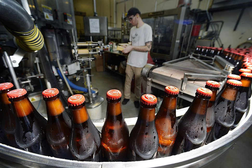 Scott Sommerdorf | The Salt Lake Tribune Bottles of HooDoo Golden Ale travel down Uinta Brewing's facility packaging line, Thursday, July 20, 2017. It's one of several 3.2 beers Uinta makes for the Utah market.