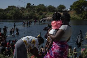 """(Veronica G. Cardenas   The New York Times)  People seeking asylum are seen crossing the Rio Grande into Del Rio, Texas on Friday, Sept. 17, 2021. Haiti migration officials have asked the United States for a """"humanitarian moratorium"""" even as they prepare to receive the first returnees from Texas. """"Will we have enough to feed these people?"""""""