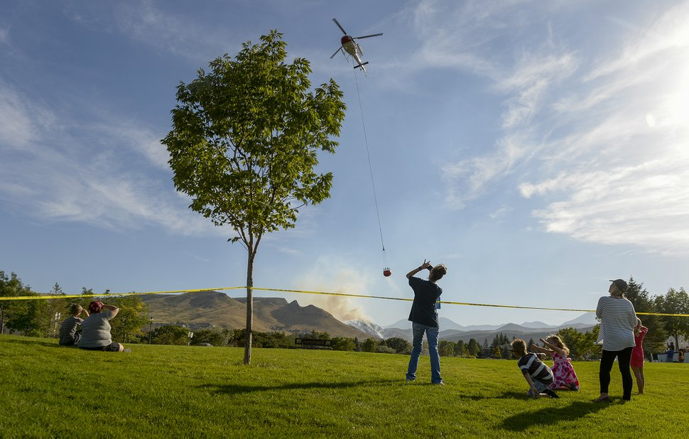 (Leah Hogsten | The Salt Lake Tribune) Homeowners who were not allowed to return to their homes and onlookers waited near Herriman Cove pond to watch as a firefighting helicopter refilled. A 50-acre wildfire in Rose Canyon was threatened about a half-dozen homes Wednesday, Sept. 12, 2018. A spokesman for Unified Fire said the blaze has already burned a few structures, including outhouses and sheds. Firefighters have evacuated around 20 to 30 homes in two neighborhoods near 15555 S. Rose Canyon Road in Herriman.