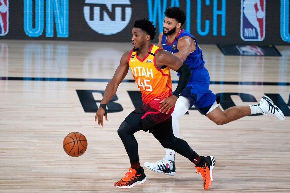 Utah Jazz's Donovan Mitchell (45) brings the ball up the court as Denver Nuggets' Jamal Murray defends during the first half of an NBA basketball first round playoff game Sunday, Aug. 30, 2020, in Lake Buena Vista, Fla. (AP Photo/Ashley Landis)