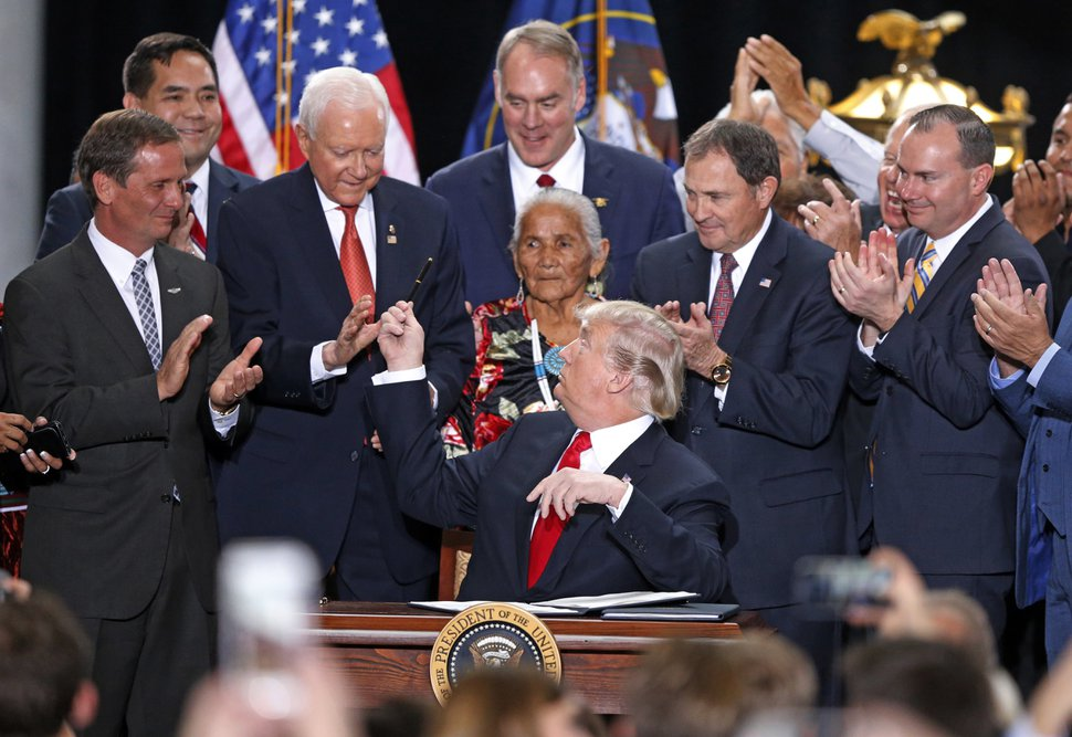 President Donald Trump hands a pen to Sen Orrin Hatch, R-Utah, after signing a proclamation to shrink the size of Bears Ears and Grand Staircase Escalante national monuments at the Utah State Capitol Monday, Dec. 4, 2017, in Salt Lake City. (AP Photo/Rick Bowmer)