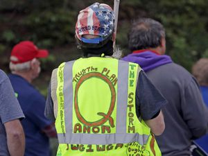 (Ted S. Warren | AP file photo) In this May 14, 2020, file photo, a person wears a vest supporting QAnon at a protest rally in Olympia, Wash.