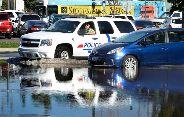 Scott Sommerdorf | The Salt Lake Tribune A Utah Transit Authority officer drives through the flooded parking lot at the Ballpark Station. Northbound Main Line TRAX trains were prevented from leaving the station due to flooding, Wednesday, July 26, 2017. Northbound riders were taken via a bus bridge to the next station.