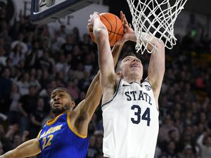 Utah State forward Justin Bean (34) shoots as San Jose State guard Richard Washington (22) defends during the first half of an NCAA college basketball game Tuesday, Feb. 25, 2020, in Logan, Utah. (Eli Lucero/The Herald Journal via AP)