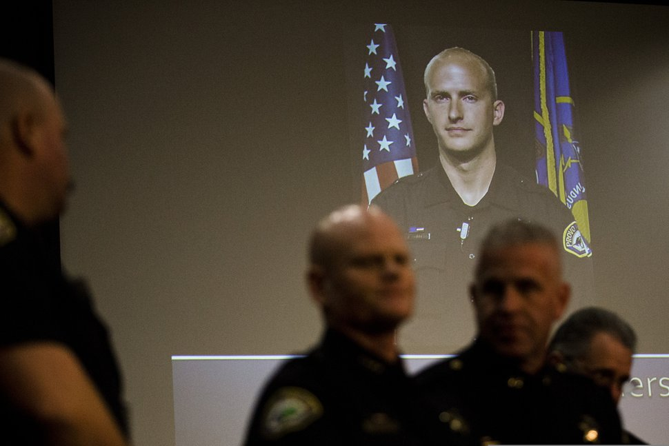 A picture of Joseph Shinners, a Provo police officer who was killed in the line of duty, is projected at the Provo City Center building during a news conference on Sunday, Jan. 6, 2019, in Provo, Utah. Shinners, who was shot and killed while trying to apprehend a fugitive, was a three-year veteran of the force who managed to shoot back and strike the suspect at least once after he was hit by gunfire. (Evan Cobb/The Daily Herald via AP)