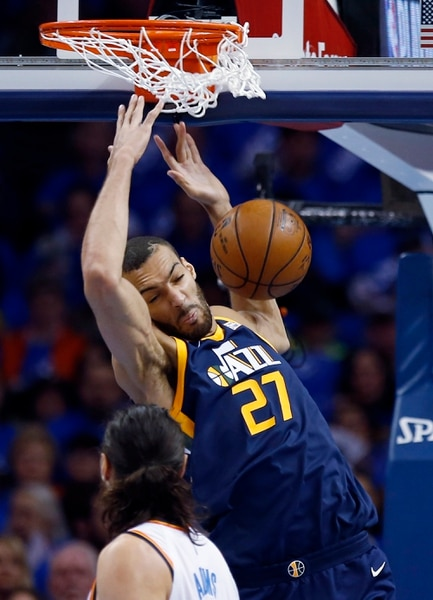 Utah Jazz center Rudy Gobert (27) dunks in front of Oklahoma City Thunder center Steven Adams in the first half of Game 1 of an NBA basketball first-round playoff series in Oklahoma City, Sunday, April 15, 2018. (AP Photo/Sue Ogrocki)