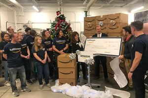 (Photo courtesy of Lauren Littlefield) Amazon fulfillment and delivery employees look on as company officials pass a check for $25,000 to VOA leaders in early December.