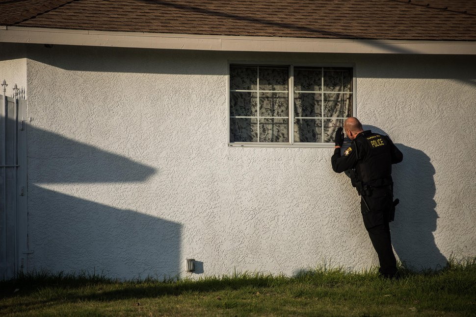 (Salwan Georges | The Washington Post) California Justice Department Special Agent Supervisor Sam Richardson looks through a side window of a home in Covina, California, as his team tries to find a resident who has a registered weapon.