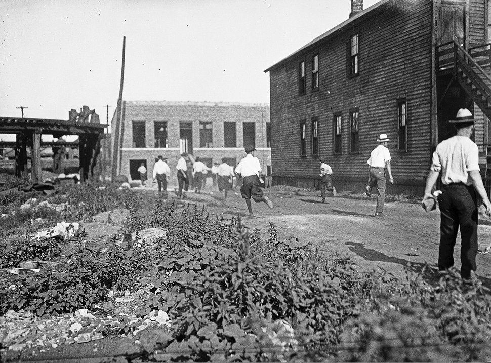 (Chicago History Museum/The Jun Fujita negatives collection via AP) In this 1919 photo provided by the Chicago History Museum, a mob runs with bricks during the race riots in Chicago. Red Summer, as the summer of 1919 came to be known, saw white-on-black violence in big cities like Washington and Chicago and small towns like Elaine, Ark., and Bisbee, Ariz.
