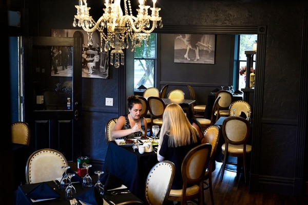 (Scott Sommerdorf   The Salt Lake Tribune) The 1920s speakeasy feel of the Charleston Cafe in Draper is accentuated by dark-painted interiors with period photos.