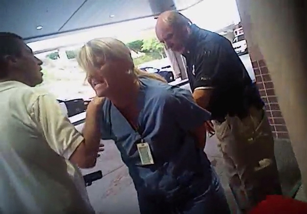(Salt Lake City Police Department/Courtesy of Karra Porter) In this July 26, 2017, frame grab from video taken from a police body camera and provided by attorney Karra Porter, nurse Alex Wubbels is arrested by a Salt Lake City police officer at University Hospital in Salt Lake City. The Utah police department is making changes after the officer dragged Wubbels out of the hospital in handcuffs when she refused to allow blood to be drawn from an unconscious patient.