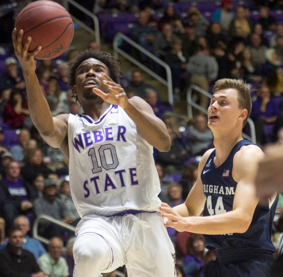 (Rick Egan | The Salt Lake Tribune) Weber State Wildcats guard Jerrick Harding (10) takes the ball to the basket, as Brigham Young Cougars guard Connor Harding (44) looks on, in basketball action between Brigham Young Cougars and Weber State Wildcats, at the Dee Event Center in Ogden, Saturday, Dec. 1, 2018.