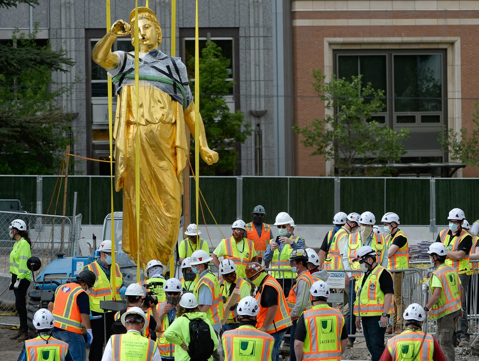 (Francisco Kjolseth   The Salt Lake Tribune) Crews and the general public gather to get a closer look of the Angel Moroni statue after it was pulled from atop the Salt Lake Temple on May 18, 2020.