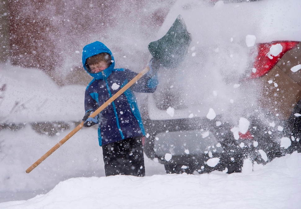(Rick Egan | The Salt Lake Tribune) With school delayed until 10 am due to the storm, 7-year-old Liam Eckersley, of Bountiful, attempts to shovel snow against the blowing wind, Monday, Feb. 3, 2020.