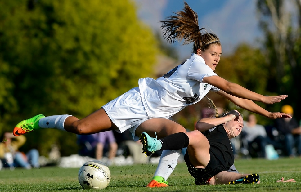 (Steve Griffin | The Salt Lake Tribune) Copper Hills defender Mariah Slick, left, collides with Davis forward Sami Bates as they fall to the ground during the Class 6A girls' soccer playoff game at Copper Hills High School in West Jordan Tuesday October 10, 2017.