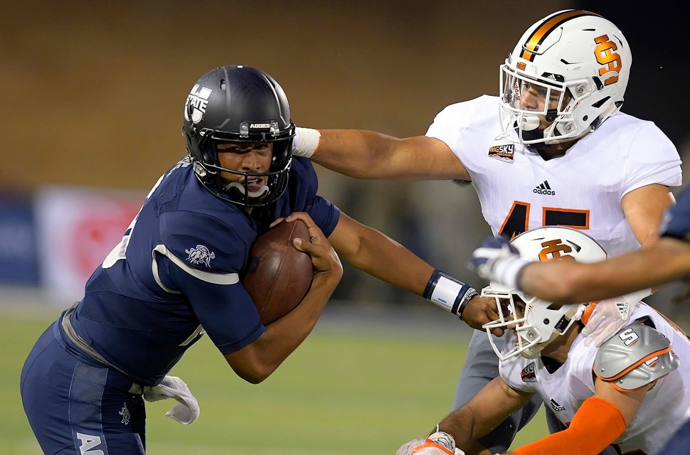 Utah State quarterback Jordan Love (10) carries the ball as Idaho State linebacker Oshea Trujillo (45) and defensive back Adkin Aguirre defend during an NCAA college football game Thursday, Sept. 7, 2017, in Logan, Utah. (Eli Lucero/Herald Journal via AP)