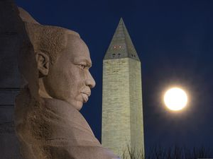 The rising full moon passes behind the Martin Luther King Memorial and the Washington Monument, Tuesday evening, Dec. 29, 2020, in Washington. (AP Photo/J. David Ake)