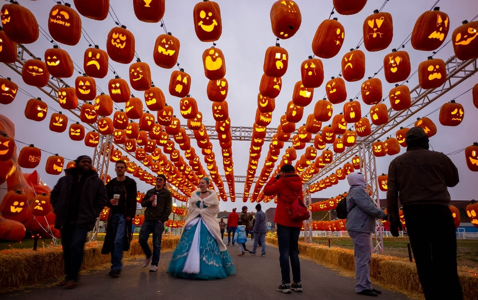 (Trent Nelson | The Salt Lake Tribune) Visitors walk through the Pumpkin Passage at Pumpkin Nights at the Utah State Fairpark in Salt Lake City on Monday, Oct. 28, 2019.