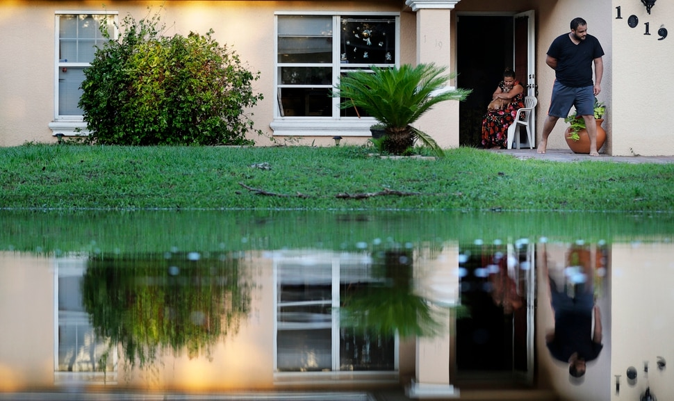 Sandra Pagan, left, escapes the heat inside her home with her dog Goldo and nephew Misael Fernandez after Hurricane Irma flooded their neighborhood leaving them without power and impassable with their cars in Fort Myers, Fla., Tuesday, Sept. 12, 2017. It's unbearable, said Pagan who rode out the storm in the home with her family. We can't sleep at all. It's so hot. (AP Photo/David Goldman)