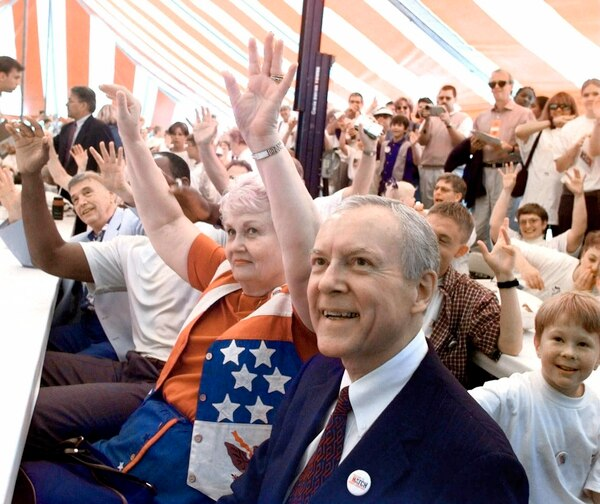 Republican presidential hopeful Orrin Hatch, foreground, smiles as his wife, Elaine, shown seated next to Hatch, and others follow the directions of an entertainer performing at a Hatch for President rally in Ames, Iowa, prior to the Iowa Straw Poll Saturday, Aug. 14, 1999. (AP Photo/Cliff Schiappa)