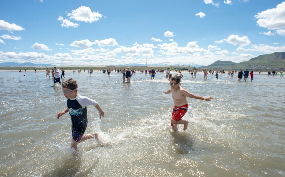(Rick Egan | The Salt Lake Tribune) Brave kids ignore the cold temperature as they splash through the water at the Great Salt Lake Saturday, June 8, 2019. The cool temperatures resulted in a crowd of around 300 people, so the attempt to break the world record was turned into a polar plunge.