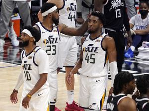 Utah Jazz forward Royce O'Neale, center, pats guard Donovan Mitchell, right, on the head as guard Mike Conley walks away in the closing minutes during the second half in Game 6 of a second-round NBA basketball playoff series against the Los Angeles Clippers Friday, June 18, 2021, in Los Angeles. (AP Photo/Mark J. Terrill)