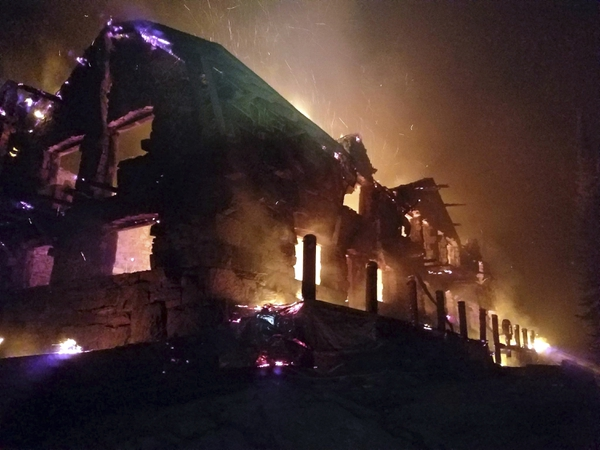 FILE - This Aug. 31, 2017, file image from video provided by the Hutton Incident Team shows the historic main Sperry Chalet building engulfed in flames in Glacier National Park, Mont. The National Park Service has approved plans to rebuild a century-old Montana hikers' dormitory that was destroyed in a fire last year in Glacier National Park. Glacier park spokeswoman Lauren Alley said Thursday, May 17, 2018, that work to reconstruct the Sperry Chalet is expected to begin in July after officials determined this week there would be no significant environmental impact. (Hutton IncidentTeam via AP, File)