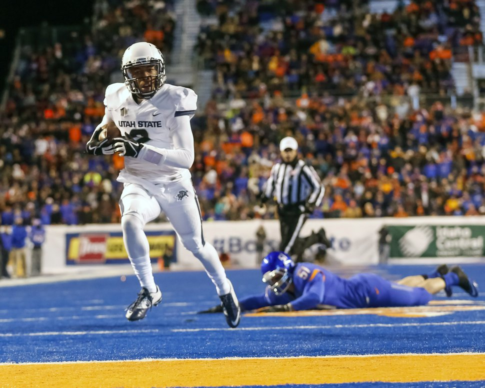 Utah State quarterback Kent Myers (2) runs for a touchdown during the first quarter of an NCAA college football game against Boise State in Boise, Idaho, on Saturday, Nov. 29, 2014. (AP Photo/Otto Kitsinger)