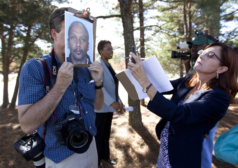 (John Bazemore | The Associated Press) Members of the media copy a police photo of shooting suspect Floyd Palmer outside the World Changers International church in College Park, Ga., after a fatal shooting inside Wednesday, Oct. 24, 2012. Police say a volunteer leading a prayer service was shot and killed by a former church employee.