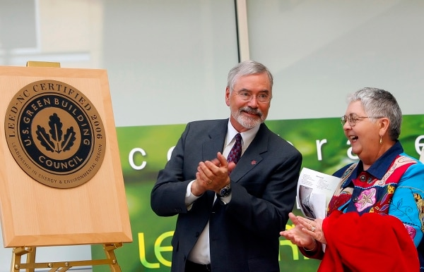 Chris Detrick | Tribune file photo A. Lorris Betz, M.D., Ph.D., Office of the Senior Vice President for Health Sciences, left, and Linda Amos, Former Associate VP health Sciences Center, unveil an award from the Leadership in Energy and Environmental Design (LEED) Certificate by the U.S. Green Building Council. April 13, 2006.