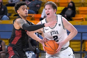 Utah State guard Sean Bairstow (2) drives to the basket as San Diego State guard Trey Pulliam defends during the first half of an NCAA college basketball game Thursday, Jan. 14, 2021, in Logan, Utah. (Eli Lucero/The Herald Journal via AP, Pool)