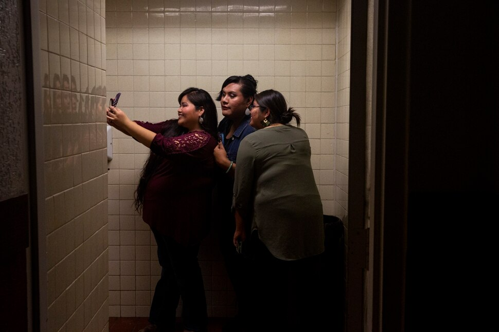 (Adriana Zehbrauskas | The New York Times) Girls take a bathroom selfie during a concert by Stateline, a Navajo country band, in Gallup, N.M., Nov. 6, 2019. At highway honky-tonks, casino lounges and far-flung dance halls, a form of music that many associate with rural white America is flourishing in the heart of Indian country, and no tribe have put their own stamp on country music quite like the Navajo.