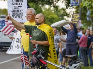 (Leah Hogsten | The Salt Lake Tribune) Protesters waving American flags and holding signs decrying mask and vaccine mandates gathered along the curb of 700 East in Liberty Park Saturday, making Salt Lake City one of dozens of cities around the world protesting public health-related restrictions, Sept. 18, 2021.