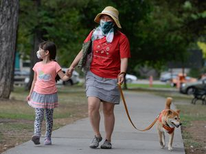 (Francisco Kjolseth     The Salt Lake Tribune) Ikue Chambless is joined by her daughter Shiona, 5, as they walk their dog Kaemon at Liberty Park in Salt Lake City while wearing masks due to COVID-19 on Wednesday, July 22, 2020.