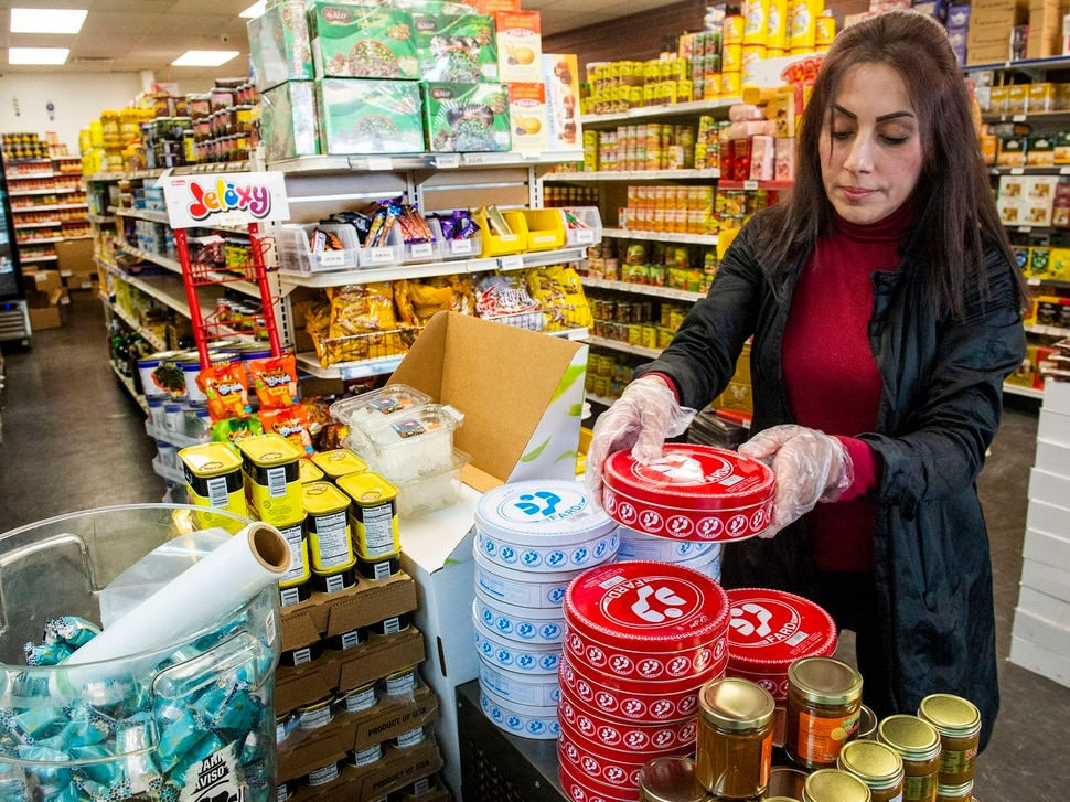 (Rick Egan | The Salt Lake Tribune) Leila Sabat straightens food on the shelves of the Specialty Market in Midvale, which is suffering from the effects of COVID-19 Wednesday, March 25, 2020.