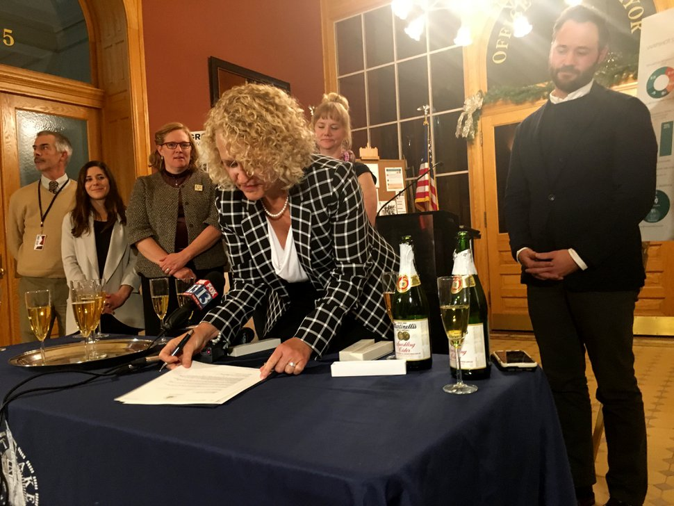 Mayor Jackie Biskupski signs an executive memo on housing policy Tuesday night, Dec. 12, 2017, moments after the City Council approved a new comprehensive housing policy for the city to guide development over the next five years.