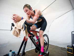 (Tommy Zaferes/contributed photo) Two-time U.S. Olympian Katie Zaferes trains on her bike in a tent equipped with a heater and humidifier that takes temperatures above 90 degrees and humidity around 80% — similar conditions to those she'll face in Tokyo for the Olympics in the coming weeks.