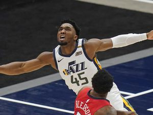 Utah Jazz guard Donovan Mitchell (45) watches  after laying the ball up over New Orleans Pelicans guard Eric Bledsoe (5) duirng the first half of an NBA basketball game Thursday, Jan. 21, 2021, in Salt Lake City. (AP Photo/Rick Bowmer)