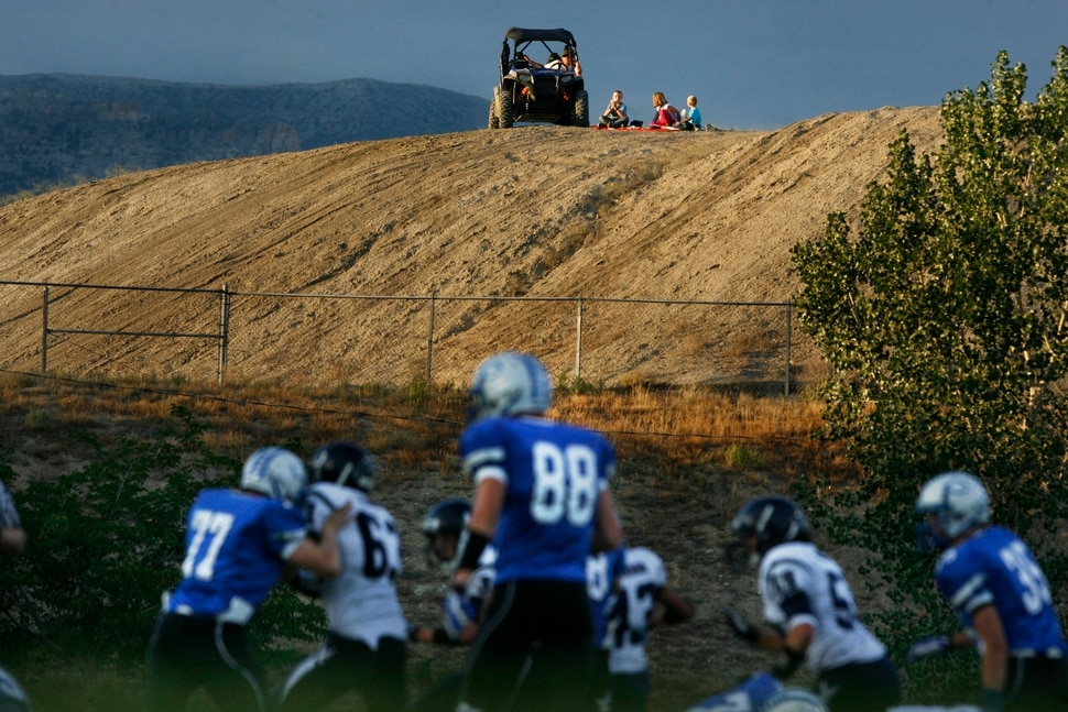 (Scott Sommerdorf | The Salt Lake Tribune) Duchesne and Carbon play as a family watches from a hilltop near the Carbon High football field. The Eagles would go on to an easy 35-0 win against Carbon High which ran their winning streak to 37 games, setting the Utah state record for consecutive wins, Friday, September 6, 2013.